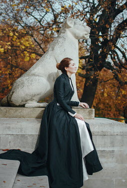Irina Orwald Young woman in Victorian dress sitting by lion sculpture