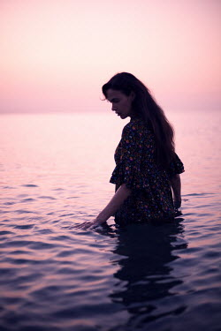 Ebru Sidar Young woman in floral dress wading in sea