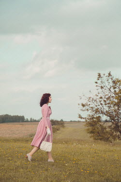 Joanna Czogala Young woman with vintage pink dress and purse in field