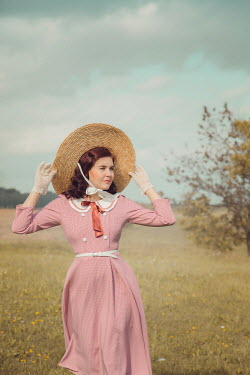 Joanna Czogala Young woman with vintage pink dress and straw hat in field