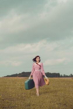 Joanna Czogala Young woman with vintage pink dress and suitcase in field
