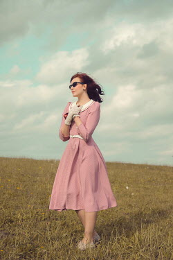 Joanna Czogala Young woman with vintage pink dress and sunglasses in field