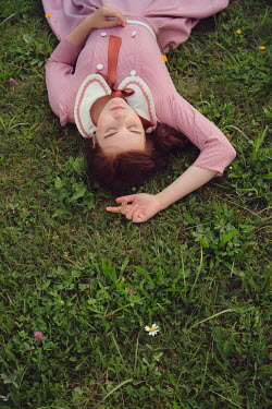 Joanna Czogala Young woman in vintage pink dress lying in grass