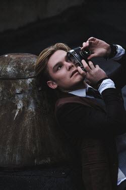 Natalia Ciobanu Young man taking photograph while leaning on bollard