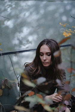 Natalia Ciobanu BRUNETTE WOMAN SITTING IN GARDEN IN AUTUMN Women