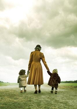 Stephen Mulcahey A mother holding hands with her children Children