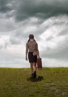 Stephen Mulcahey GIRL CARRYING SUITCASE WALKING IN FIELD Children
