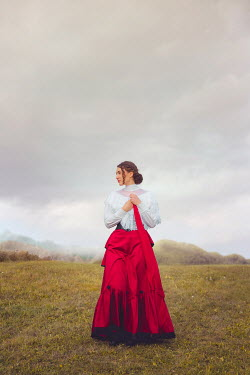 Joanna Czogala HISTORICAL WOMAN HOLDING SCARF IN COUNTRYSIDE Women