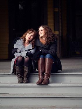 Elisabeth Ansley TWO FEMALE FRIENDS SITTING ON PORCH SMILING Women