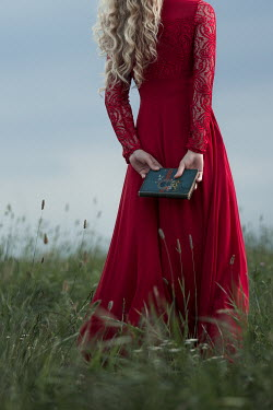 Magdalena Russocka woman in red dress with book standing in field