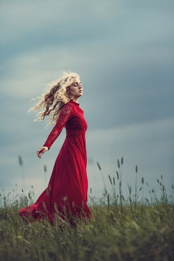 Magdalena Russocka woman in red dress standing in field