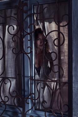 Alex Maxim BRUNETTE WOMAN PEERING FROM WINDOW AT DUSK Women