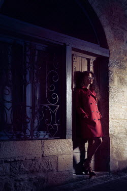 Alex Maxim WOMAN IN RED COAT IN DOORWAY AT NIGHT Women