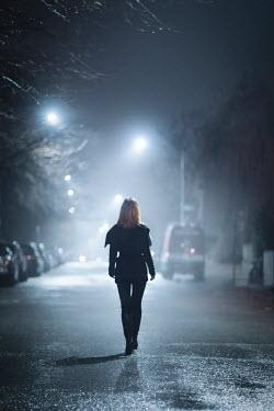 Evelina Kremsdorf WOMAN WALKING IN URBAN STREET AT NIGHT Women
