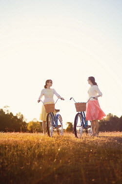 Susan Fox TWO GIRLS WITH BICYCLES IN SUMMERY COUNTRYSIDE Women