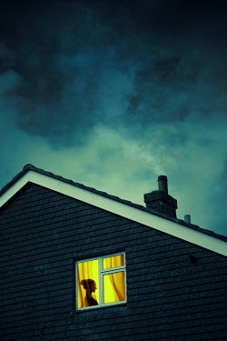 Magdalena Russocka silhouetted woman in window of house at dusk