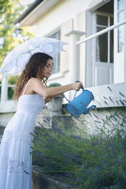 Alex Maxim WOMAN WITH PARASOL WATERING LAVENDER IN GARDEN Women