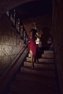 Alex Maxim WOMAN DESCENDING STAIRCASE IN DARK OLD HOUSE Women