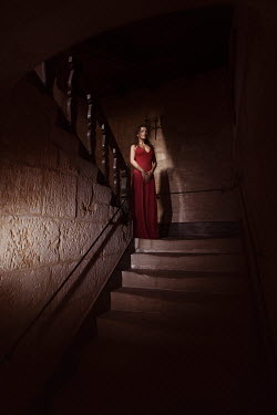 Alex Maxim WOMAN STANDING ON STAIRCASE IN DARK OLD HOUSE Women