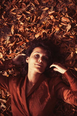 Esmahan Ozkan WOMAN LYING ON AUTUMN LEAVES FROM ABOVE Women