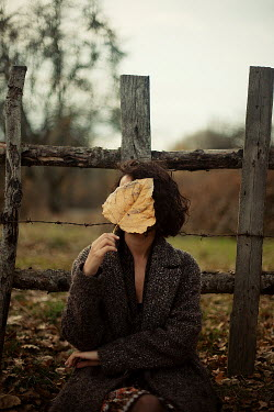 Esmahan Ozkan WOMAN COVERING FACE WITH LEAF IN WINTER OUTDOORS Women