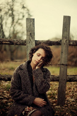 Esmahan Ozkan WOMAN SITTING DAYDREAMING BY FENCE IN COUNTRY Women