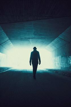 Ildiko Neer Silhouetted man walking in tunnel
