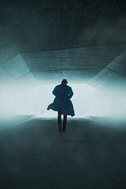 Ildiko Neer Silhouetted man running in tunnel