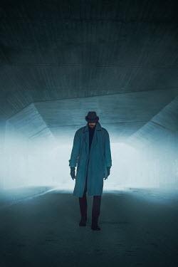 Ildiko Neer Man in overcoat walking in tunnel