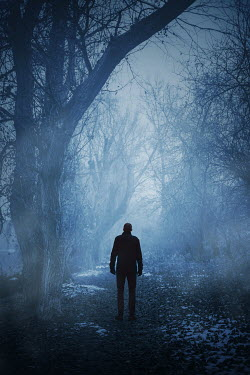 Ildiko Neer Man in black coat standing by trees