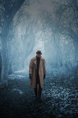 Ildiko Neer Man in overcoat walking by trees