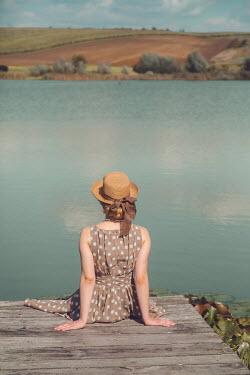 Joanna Czogala WOMAN IN HAT SITTING ON JETTY BY LAKE Women