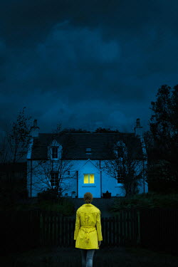 Magdalena Russocka woman standing at gate of old cottage house at night