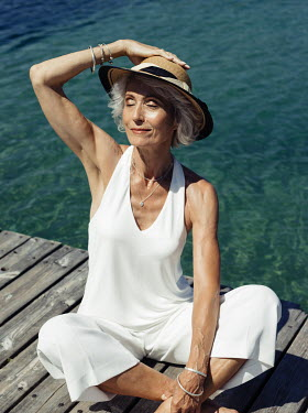 Nina Masic MATURE WOMAN IN HAT SITTING ON JETTY Old People