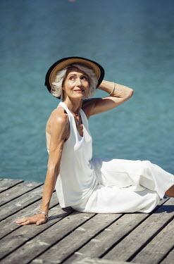 Nina Masic MATURE WOMAN IN HAT SITTING ON JETTY Women