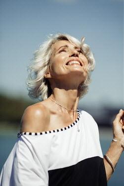 Nina Masic HAPPY MATURE WOMAN BY LAKE IN SUMMER Women