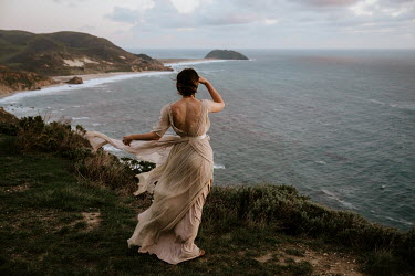Paige Nelson WOMAN IN SILK DRESS ON WINDY CLIFF BY SEA Women