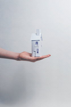 Catherine Macbride HAND HOLDING MODEL OF SMALL PAPER HOUSE Body Detail