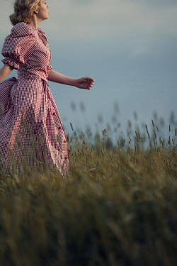 Magdalena Russocka retro woman in gingham dress running in field