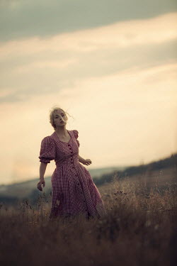 Magdalena Russocka retro woman in gingham dress running in field at sunset