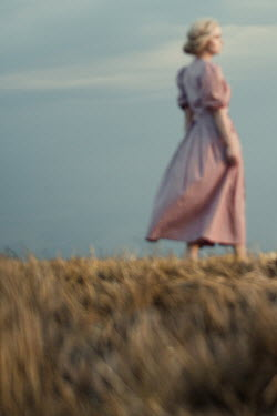 Magdalena Russocka retro woman in gingham dress walking in field