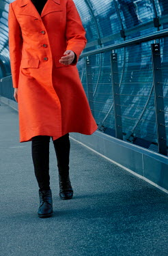 Ute Klaphake Woman in orange coat walking on pedestrian bridge