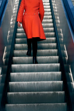 Ute Klaphake Woman in orange coat on escalator
