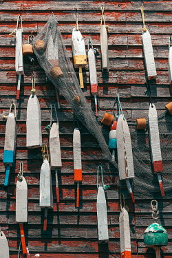 Alicia Bock Wooden buoys and net hanging on wall of fishing shack