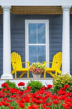 Evelina Kremsdorf Yellow adirondack chairs on porch with flowers