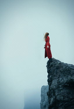 Natasza Fiedotjew Silhouette of young woman in red coat standing on edge of cliff