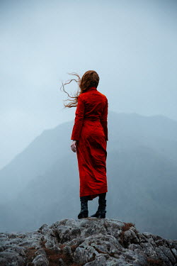 Natasza Fiedotjew Young redhead woman in red coat standing in mountains on rainy day