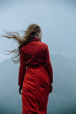 Natasza Fiedotjew Young redhead woman in red coat standing in rain