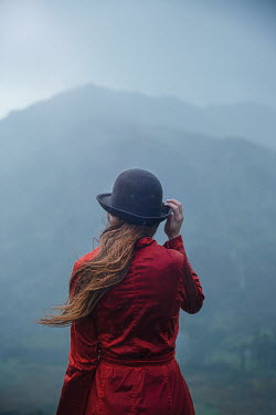 Natasza Fiedotjew Young woman in red coat and hat looking at mountains in rain