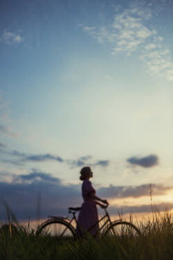 Magdalena Russocka retro woman with bike standing in field at sunset